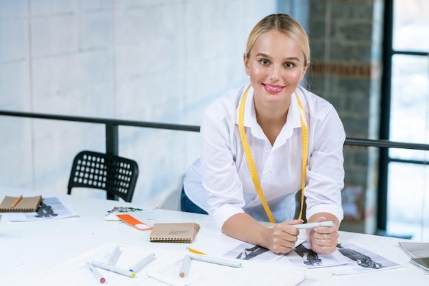 Dość młoda blond projektantka mody patrzy na ciebie pochylając się nad biurkiem podczas pracy ze szkicami w studio