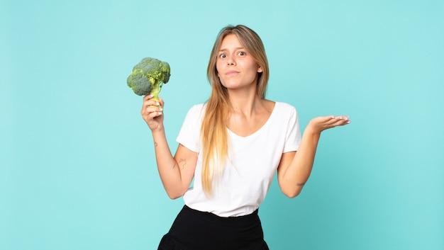 Dość młoda blondynka trzyma brokuły