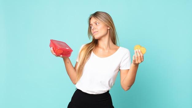Dość młoda blondynka trzyma tupperware