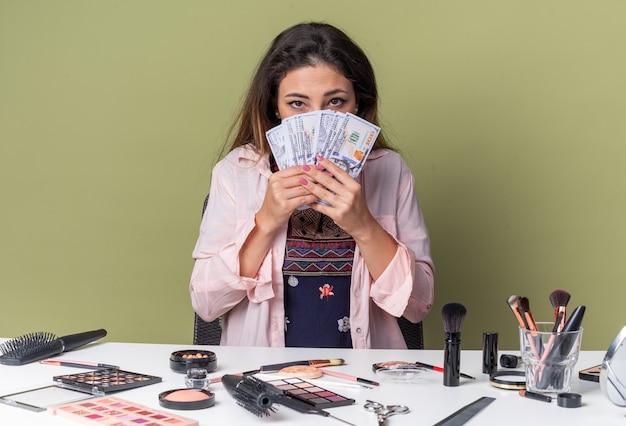 Dość młoda brunetka dziewczyna siedzi przy stole z narzędziami do makijażu, trzymając pieniądze