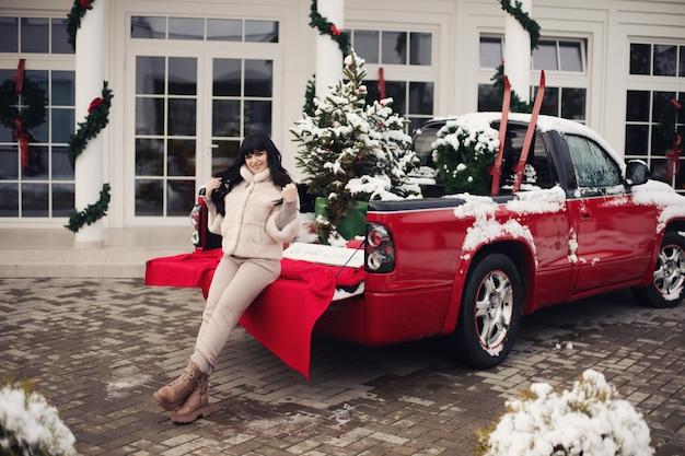 Dość młoda brunetka kobieta ubrana w ciepłe zimowe ubrania pozuje w pobliżu samochodu z dekoracjami świątecznymi w pobliżu domu na świeżym powietrzu.