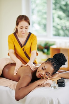 Dość młoda czarna kobieta spędza dzień w salonie spa i ciesząc się relaksującym masażem pleców