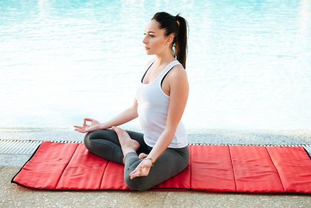 Dość młoda dama fitness robi ćwiczenia jogi w pobliżu basenu.