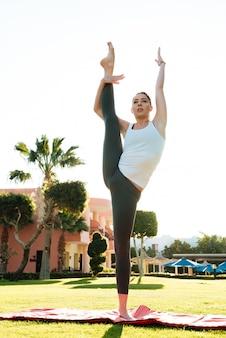 Dość młoda dama fitness robi ćwiczenia rozciągające