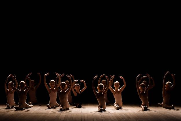 Dość młoda dziewczyna i chłopak siedzi na scenie o rozciąganie i szkolenie do tańców baletowych.
