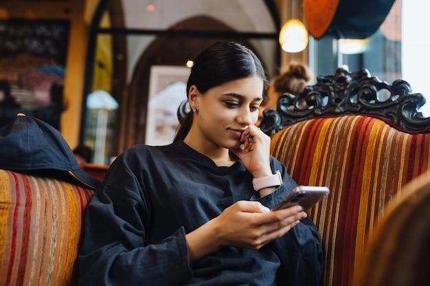 Dość młoda dziewczyna odpoczywa na dużym miękkim krześle w kawiarni, rozmawia przez telefon, rozmawia czas
