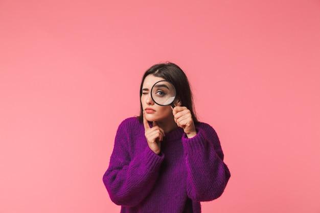 Dość młoda dziewczyna ubrana w sweter stojący na białym tle nad różowym, patrząc przez szkło powiększające