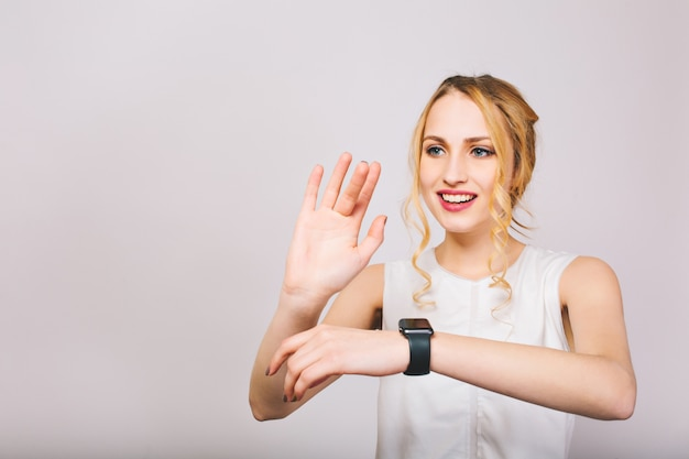 Dość młoda jasnowłosa dama macha rękami i pozuje z uśmiechem na białym tle. urocza dziewczyna z kręconymi włosami, ubrana w stylowy podkoszulek, śmiejąca się i pokazująca nowy czarny zegarek