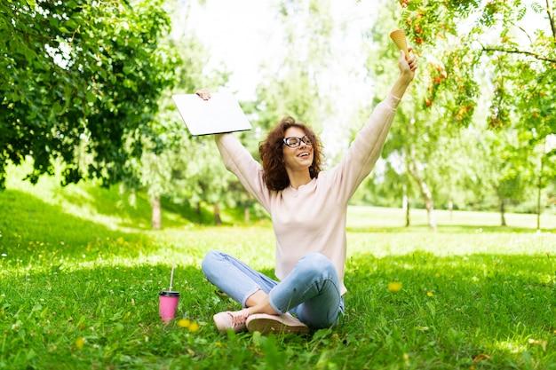 Dość młoda kaukaska kobieta idzie na spacer do parku, siedzi na trawie i raduje się