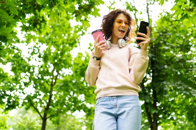 Dość młoda kaukaska kobieta idzie na spacer do parku z filiżanką kawy i komunikuje się z przyjaciółmi za pomocą swojego telefonu