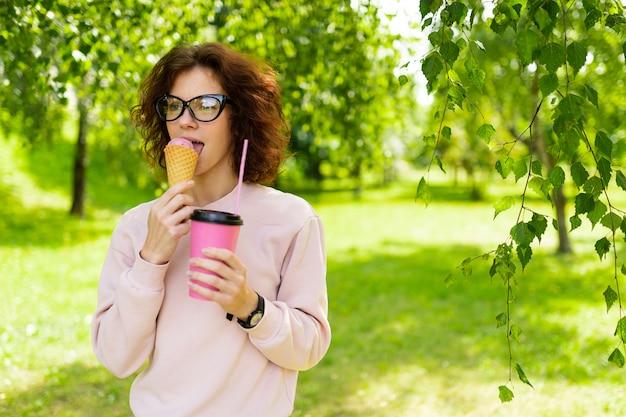 Dość młoda kaukaska kobieta idzie na spacer do parku z kawą i lodami