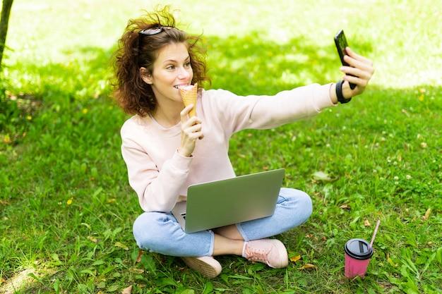 Dość młoda kaukaska kobieta jest niezależna w parku z laptopem, filiżanką kawy i lodów, siada na trawie i robi selfie
