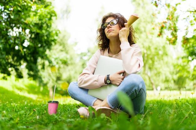 Dość młoda kaukaska kobieta myśli o czymś w parku z laptopem, filiżanką kawy i lodami