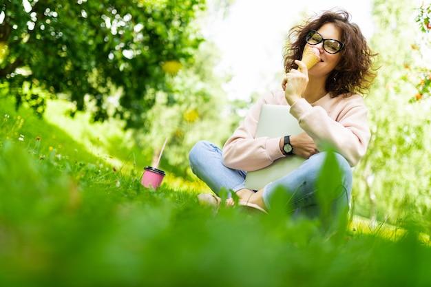 Dość młoda kaukaska kobieta pracuje w parku z laptopem, filiżanką kawy i lodami