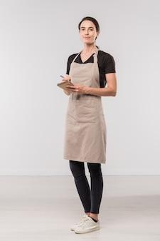 Dość młoda kelnerka kawiarni robi notatki o zamówieniu klienta, stojąc przed kamerą w izolacji