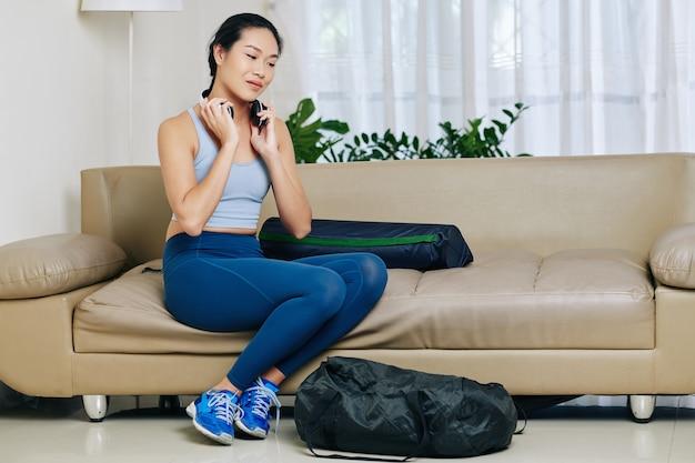 Dość młoda kobieta azji w strojach sportowych siedzi na kanapie w salonie i nakłada headphe, aby słuchać muzyki podczas joggingu