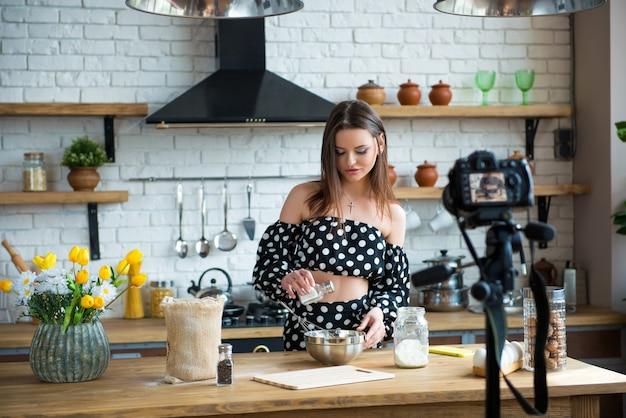 Dość młoda kobieta blogerka kulinarna w sukience w kropki pracuje nad nowym filmem i wyjaśnia, jak ugotować danie.