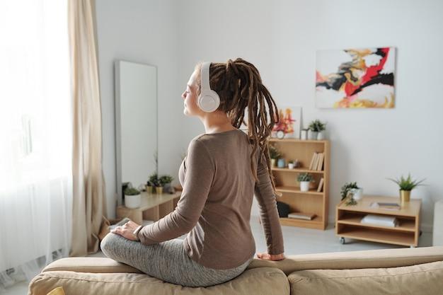 Dość młoda kobieta dorywczo z dredami, ciesząc się muzyką medytacyjną w słuchawkach, siedząc na kanapie
