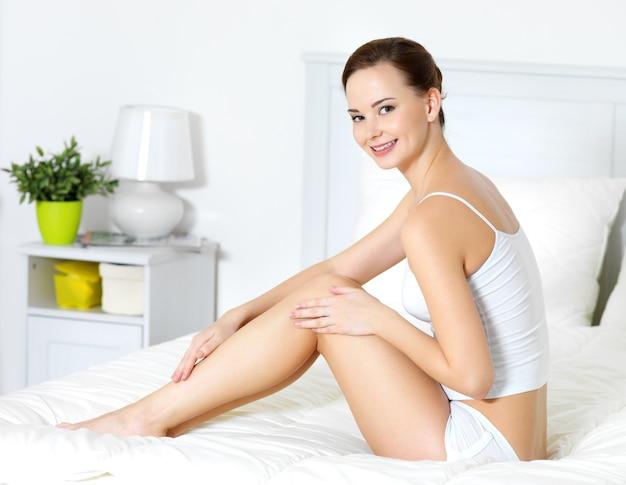Dość młoda kobieta dotyka jej pięknych nóg w dedroom