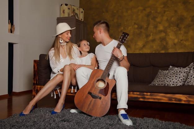 Dość młoda kobieta i mężczyzna z czteroletnią córką dziewczynki z gitarą we wnętrzu pokoju. szczęśliwa rodzina z gitarą. koncepcja nauki w domu lub gry na gitarze w domu. przestrzeń praw autorskich dla witryny