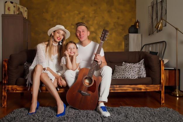 Dość młoda kobieta i mężczyzna z czteroletnią córką dziewczynki z gitarą we wnętrzu pokoju. szczęśliwa rodzina z gitarą
