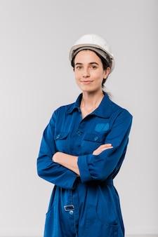Dość młoda kobieta inżynier z krzyżowym uzbrojeniem w niebieskiej odzieży roboczej i kasku stojącym w izolacji
