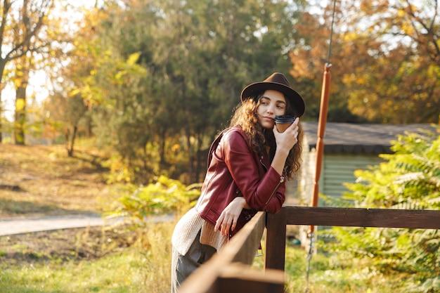 Dość młoda kobieta kręcone spaceru w parku jesienią picia kawy.