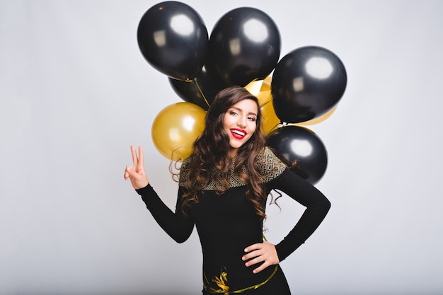 Dość młoda kobieta na białej przestrzeni trzymać złote i czarne balony. niesamowita dziewczyna z długimi kręconymi włosami, w czarnej eleganckiej sukience
