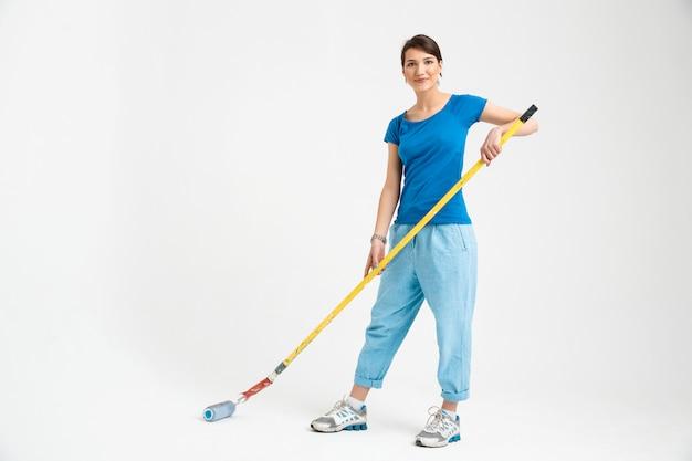 Dość młoda kobieta naprawy pokoju, trzymając wałek malarski