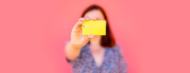 Dość młoda kobieta pokazuje pustą plastikową kartę, stoi w pobliżu różowej ściany na ulicy