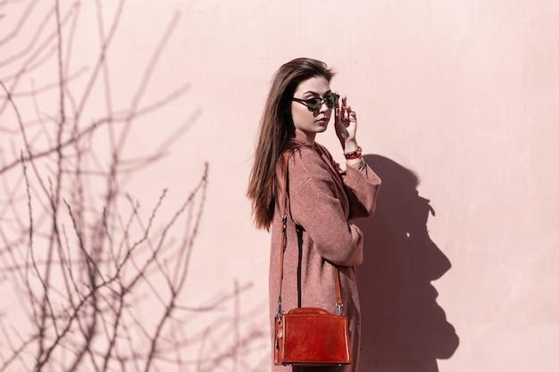Dość młoda kobieta prostuje modne okulary w pobliżu różowej ściany. piękna dziewczyna model z długimi włosami w elegancki wiosenny płaszcz ze stylową torebką pozuje w pobliżu zabytkowego budynku w słoneczny dzień. urocza pani.