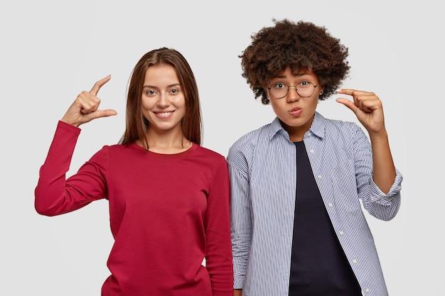 Dość młoda kobieta rasy mieszanej z ciemną skórą pokazuje kilka gestów