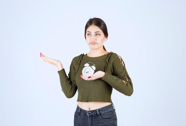 Dość młoda kobieta trzyma budzik z wyrażeniem enreadable.
