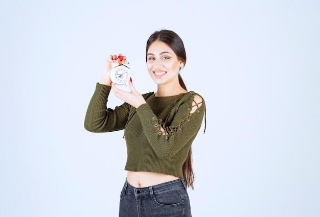 Dość młoda kobieta trzyma budzik ze szczęśliwym wyrażeniem.