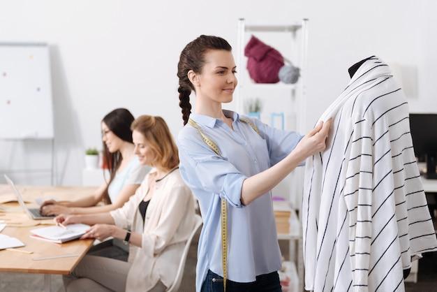 Dość młoda kobieta trzyma klapy swetra wiszące na manekinie, podczas gdy jej koledzy opracowują szkice stroju