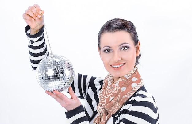 Dość młoda kobieta trzyma lustrzaną kulę.