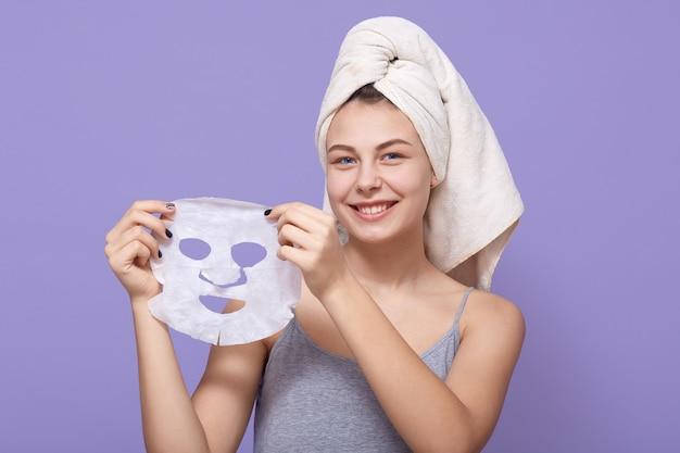 Dość młoda kobieta trzyma w rękach maskę upiększającą, która jest gotowa nałożyć ją na twarz w celu odmłodzenia
