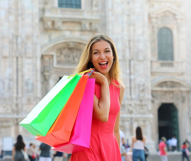 Dość młoda kobieta trzymając kolorowe torby na zakupy w mediolanie we włoszech
