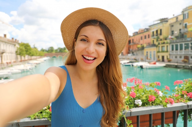 Dość młoda kobieta turysta ma autoportret nad jeziorem garda we włoszech. piękna dziewczyna mody robi zdjęcie selfie w peschiera del garda we włoszech.