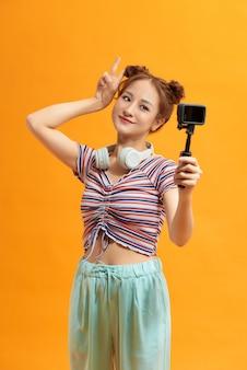 Dość młoda kobieta uśmiecha się trzymając kamerę akcji action