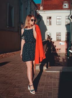 Dość młoda kobieta w czerwonej kurtce i sukience na miejskiej powierzchni ulicy miasta. stare miasto. zdjęcie pionowe