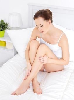Dość młoda kobieta w dedroom dotykając jej piękne nogi - w pomieszczeniu