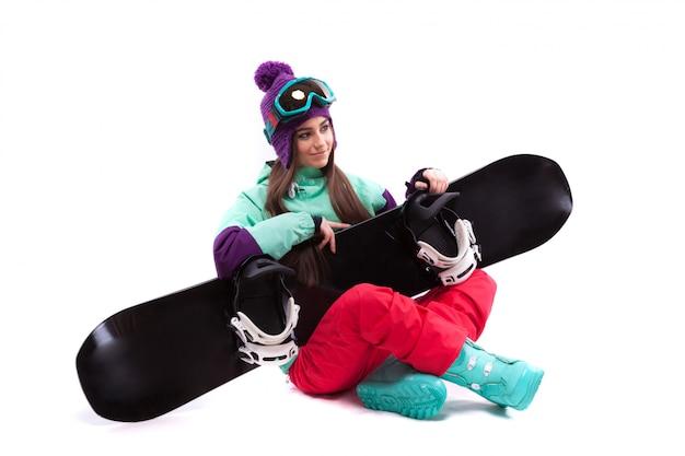 Dość młoda kobieta w fioletowym stroju narciarskim ze skrzyżowanymi nogami