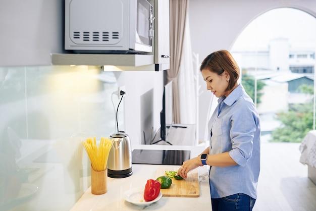 Dość młoda kobieta wietnamska cięcia świeżych warzyw podczas przygotowywania sałatki witaminowej na obiad