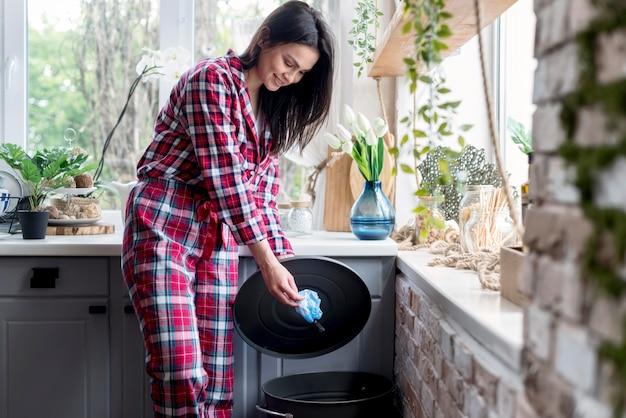 Dość młoda kobieta, wyrzucanie śmieci