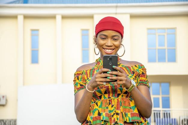 Dość młoda kobieta z afryki, uśmiechając się i używając swojego telefonu komórkowego na zewnątrz