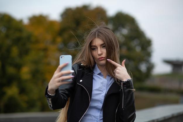 Dość młoda kobieta z długimi włosami, krzywiąc się i robiąc autoportret na telefonie komórkowym w parku