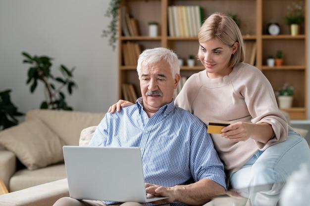 Dość młoda kobieta z kartą kredytową siedzi jej starszy ojciec z laptopem, jednocześnie robiąc zakupy online i zamierzając zapłacić za zakup