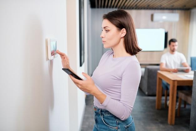 Dość młoda kobieta z ładowaniem smartfona inteligentnej aplikacji zdalnego sterowania w touchpadzie na ścianie