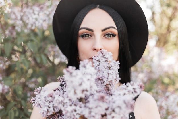 Dość młoda kobieta z pięknymi oczami w eleganckim stylowym kapeluszu trzyma w pobliżu twarzy bukiet świeżych kwiatów bzu na tle kwitnących drzew. śliczna dziewczyna spaceruje w słoneczny dzień w parku i cieszy się wiosną i słońcem.